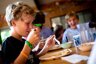 The food at camp is delicious! You eat breakfast, lunch, and dinner family-style with your cabinmates and counselor in the dining hall. The food is put on your cabin's table right before you walk inside.