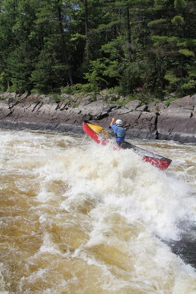 Andy Suleskey paddling hard through a large rapid in his open boat.