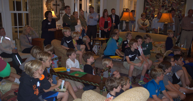 Families, campers, staff, and alumni watching the camp movie in Nashville at the McKee's home in October, 2013