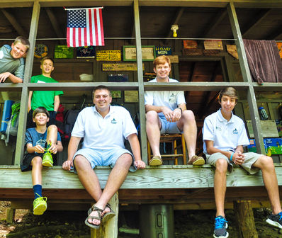 Campers and counselors gathered on a cabin porch.