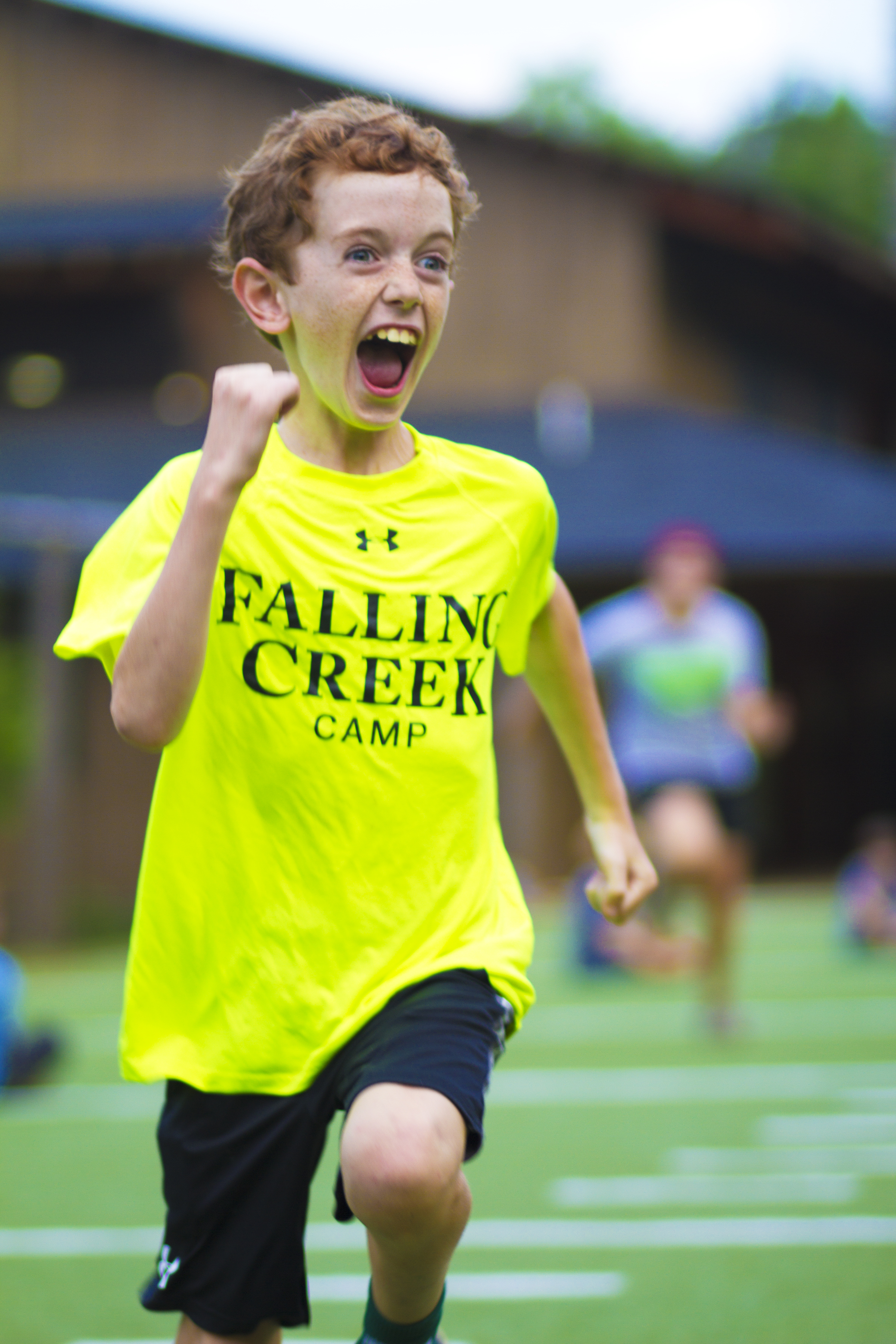Camper running with excitement on field during evening program.