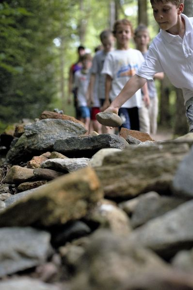 As the boys walk quietly to the final campfire for the session, they have been told earlier to bring with them a rock to drop on the right just before the bridge. Many others, before and after them, have added or will add rocks to this growing old style uneven rock wall for their final campfire of each camp session. Even dads and sons will each place a rock at their final campfire during their weekend at camp.