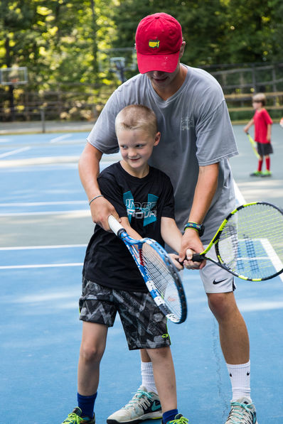 Camp counselor teaching a tennis swing to a camper.