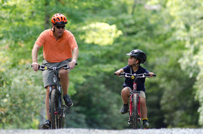 Father and son mountain biking at camp.