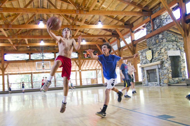 Campers playing basketball in our north carolina boys camp gymnasium.