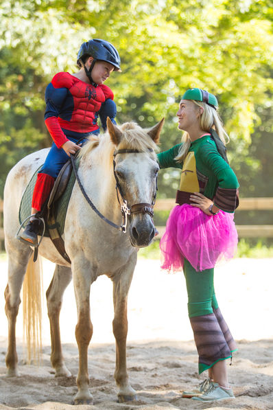 Camper and counselor dressed up for superhero day at horseback.