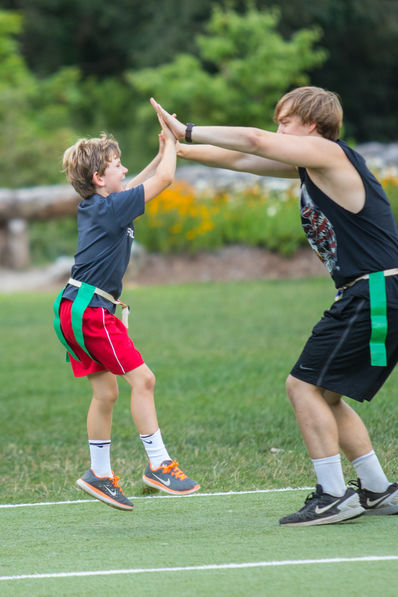 Camper and counselor give each other an enthusiastic high-five at flag football!