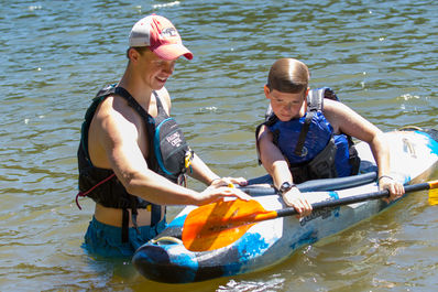 Counselor teaching a camper how to roll a kayak on our camp lake.