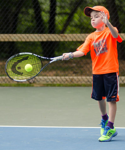 Camper playing a tennis match a camp.