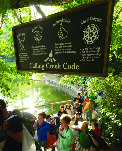 Campers walk under The Code sign during the day.