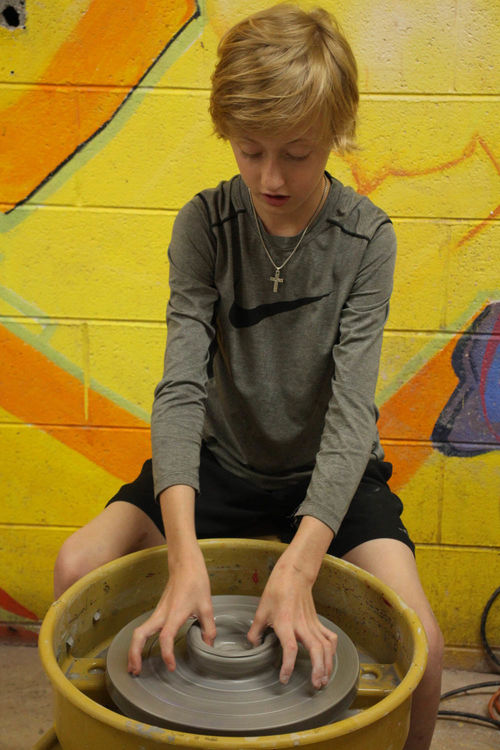 Throwing pots on the wheel in Pottery
