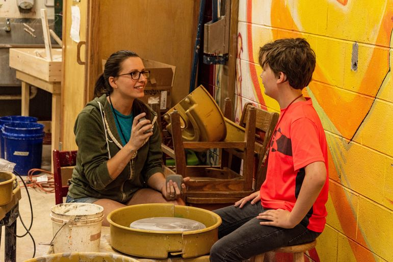Keira instructing one of the boys in her pottery class