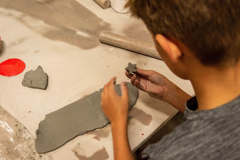 Using a slab technique to roll the clay into an even thickness, then punch out shapes with a cookie cutter for projects
