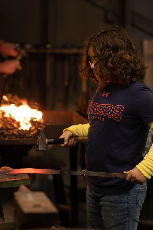Grayton forging steel at blacksmithing
