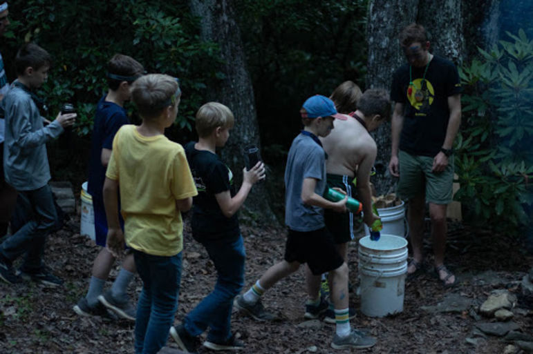 Boys contributing water to a bucket for putting out the fire