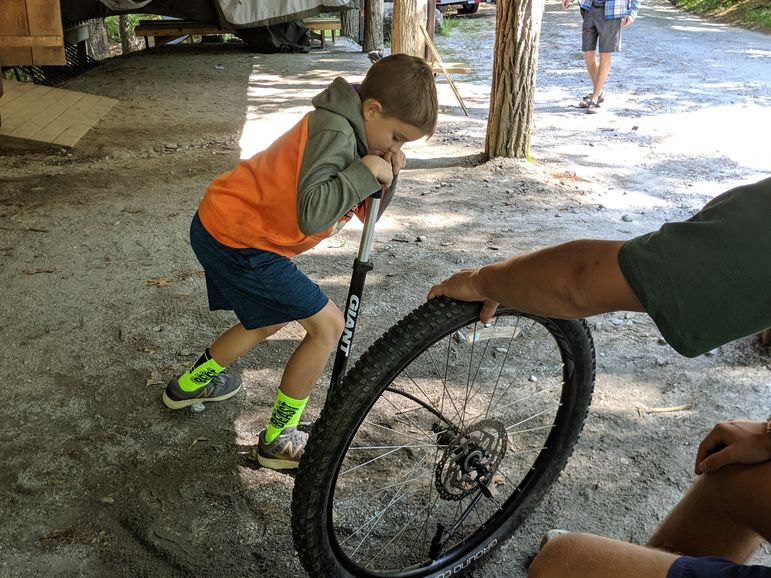 Pumping up his bike tire after practicing changing it during free-time!