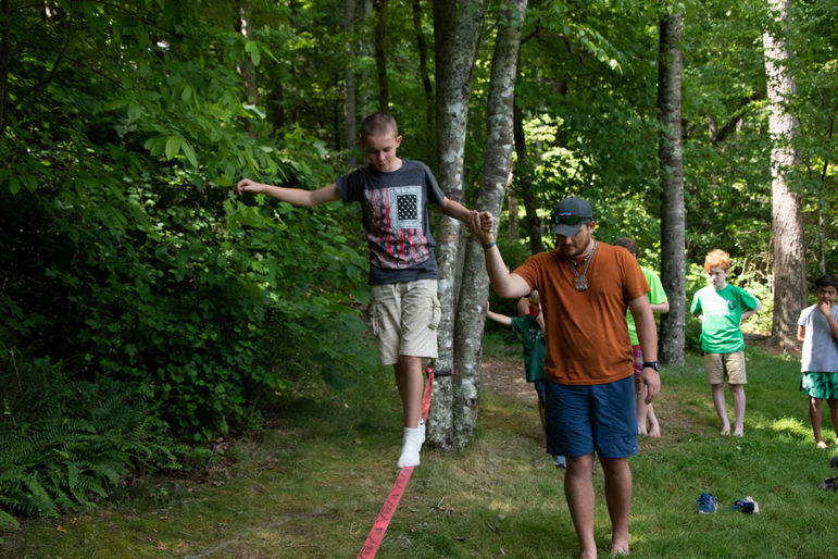 Brian helping boys find their balance while trying out slack lining