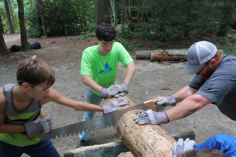 Chopping and sawing wood during the service component of last year's Journey