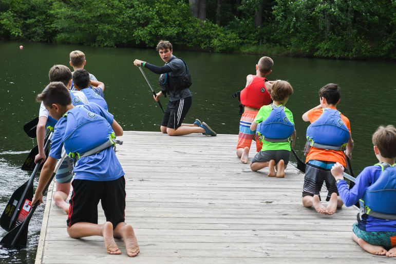 Patrick McGrady, a long-time camper and now paddling counselor, instructing a group of boys on the dock.